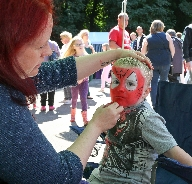 Three year old Harry gets his face painted by Emma