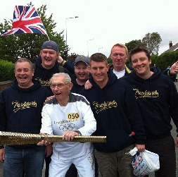 Torchbearer Norman Wells, 91, with members of the
